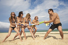 Tug-of-war on the beach. Tug-of-war between girls and guy on the beach royalty free stock photo