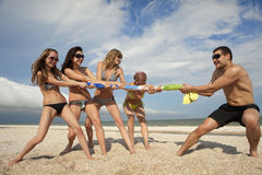 Tug-of-war on the beach. Tug-of-war between girls and guy on the beach Royalty Free Stock Images