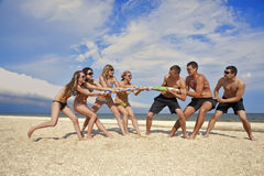 Tug-of-war on the beach. Tug-of-war between girls and guys on the beach royalty free stock images