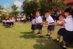 Tug of war children sporting even. Nakornratchasima , Thailand - November 4: unidentified children on fun compete in tug of war on the Field during Children's Royalty Free Stock Image