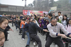 Tug-of-war. Chinese people pulling rope in tug-of-war at the stadium Stock Image