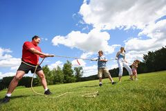 Tug Of War Between Dad And Kids Royalty Free Stock Images