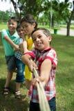 Tug of war. Joyful children playing tug of war outdoors Stock Photo