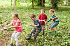 Tug-of-war in park. Group of happy smiling kids playing tug-of-war with rope in green park Stock Photo