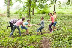 Tug-of-war in park. Group of happy smiling kids playing tug-of-war with rope in green park Stock Photos