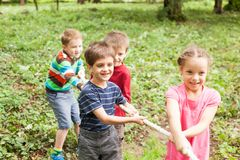 Tug-of-war in park. Group of happy smiling kids playing tug-of-war with rope in green park Stock Photography