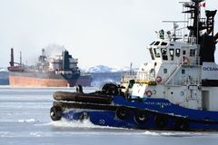 Tug woking with icy conditions stock photography