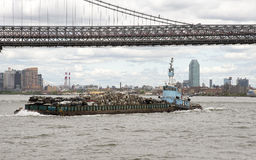 Tug working with barge on East River New York USA Stock Photo