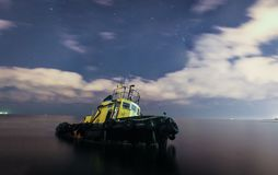 Tugboat έτρεξε τον προσαραγμένο, έναστρο νυχτερινό ουρανό με τα σύννεφα στοκ εικόνα