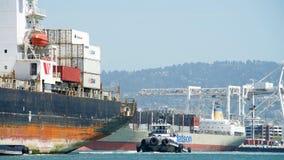 Tugboat ζ-ΤΕΣΣΕΡΑ στην πρύμνη του φορτηγού πλοίου SEASPAN NINGBO στοκ φωτογραφία με δικαίωμα ελεύθερης χρήσης