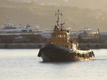 Tugboat στο θαλάσσιο λιμένα, αναμμένο από τις ακτίνες του ήλιου ρύθμισης Στοκ εικόνες με δικαίωμα ελεύθερης χρήσης