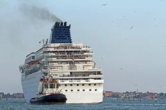 Tugboat while accurately manoeuvre the large cruise ship out of Royalty Free Stock Photos