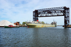 Tugboat Assist. A small tugboat towing a Great Lakes bulk carrier freighter passes under a railroad drawbridge on the Cuyahoga River in Cleveland, Ohio stock photography