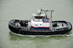 Tugboat  assisting with berthing of cargo vessel, New York Bay. royalty free stock photos