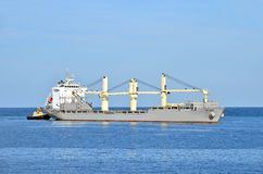 Tugboat assisting bulk cargo ship Royalty Free Stock Images