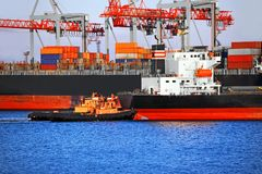 Tugboat assisting bulk cargo ship Stock Images