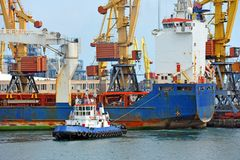 Tugboat assisting bulk cargo ship Stock Image