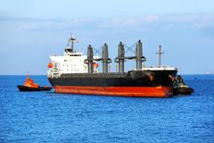 Tugboat assisting bulk cargo ship Royalty Free Stock Photo