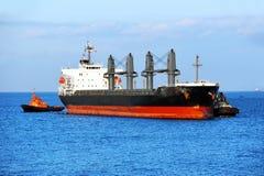 Tugboat assisting bulk cargo ship. To harbor quayside royalty free stock photo