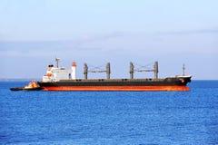 Tugboat assisting bulk cargo ship Royalty Free Stock Photo