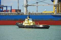 Tugboat assisting bulk cargo ship Stock Photos