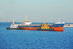 Tugboat assisting bulk cargo ship Royalty Free Stock Image
