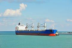 Tugboat assisting bulk cargo ship Stock Image