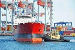 Tugboat assisting bulk cargo ship Royalty Free Stock Photos