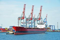 Tugboat assisting bulk cargo ship. To harbor quayside stock photos