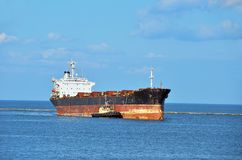 Tugboat assisting cargo ship Royalty Free Stock Image