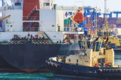 Close-up Tugboat assisting Cargo Ship maneuvered into the Port of Odessa, Ukraine. royalty free stock photography