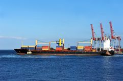 Tugboat assisting container cargo ship Royalty Free Stock Photo