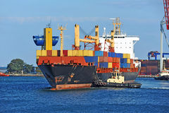 Tugboat assisting container cargo ship Royalty Free Stock Photography