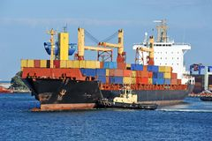 Tugboat assisting container cargo ship Stock Image