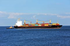 Tugboat assisting container cargo ship Stock Images