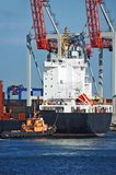 Tugboat assisting container cargo ship Stock Photos