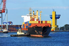 Tugboat assisting container cargo ship Royalty Free Stock Images