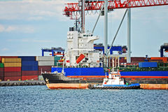 Tugboat assisting container cargo ship Royalty Free Stock Image