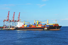 Tugboat assisting container cargo ship Stock Photography