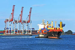 Tugboat assisting container cargo ship Royalty Free Stock Photos