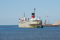 Tugboat Assisting Freighter. A Great Lakes self discharging bulk carrier ship is towed stern first by a single tugboat upbound at the entrance to the Cuyahoga stock photos