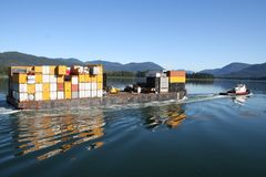 Tugboat with Barge. Tugboat navigating the calm waters of Wrangell Narrows along Southeastern Alaska's Inside Passage while towing a barge full of shipping stock photo