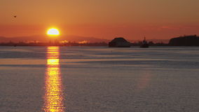 Tugboat and Barge Sunrise 4K slow motion. A tugboat towing a barge on the Fraser River near Steveston at sunrise. Vancouver, British Columbia, Canada. 4K. UHD stock video footage