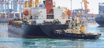 Tugboat at the bow of cargo ship , assisting the vessel to maneuver stock image