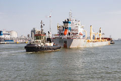 Tugboat with cargo ship in the harbor of Antwerp, Belgium Royalty Free Stock Photography