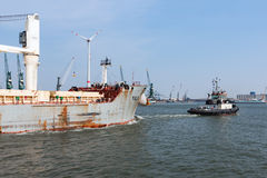 Tugboat with cargo ship in the harbor of Antwerp, Belgium Stock Images