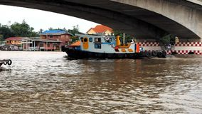 Tugboat on Chao Phraya River. A colourful tugboat passes under Rama IV bridge on Chao Phraya River on October 25, 2017  in Nonthaburi province, Thailand stock video footage