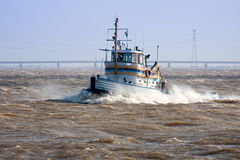 Tugboat crossing the storm. At his way to the safe harbor stock photography