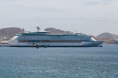 Tugboat by Cruise Ship Across Bay. A luxury cruise ship anchored in the bay on St Kitts Stock Image
