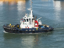 Tugboat crusing in harbor. Tugboat cruising in harbor waiting for the next ship to pull in Stock Photography
